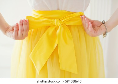 woman tying bow on her yellow skirt