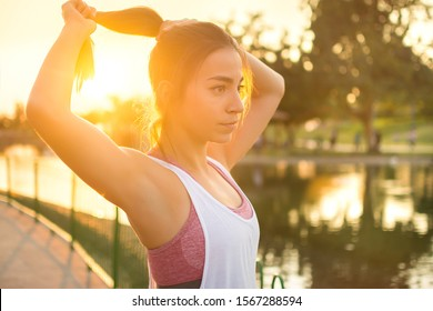 Woman tying hair in ponytail getting ready for exercising outdoors at sunset.