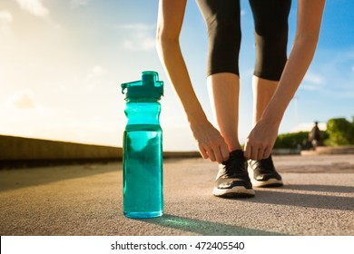 Woman tying her shoe next to bottle of water. Focus on bottle.