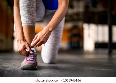 Woman tying her shoe in an open empty gym, preparing for workout or run, wearing gray leggings and royal blue top.