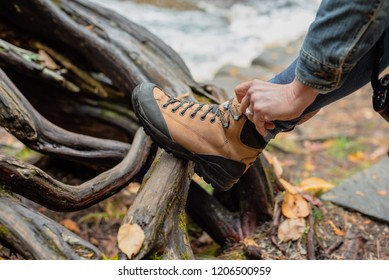 woman tying hiking boot outdoors on trail in fall