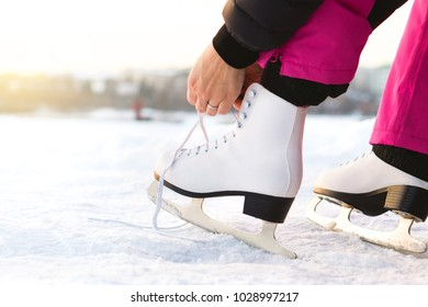 Woman tying ice skates laces by a lake or pond. Lacing iceskates. Skater about to exercise on an outdoor track or rink. Sunny winter weather for skating, sport and training in nature.