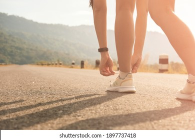 woman tying knots shoe laces,on empty road,in morning