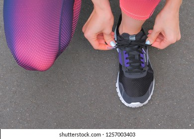 Woman tying laces of running shoes before training. Top view