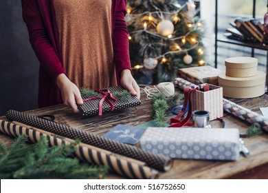 Woman Tying Ribbon on Christmas Present
