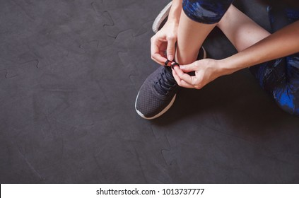 Woman tying running shoes on black floor background in gym, copy space