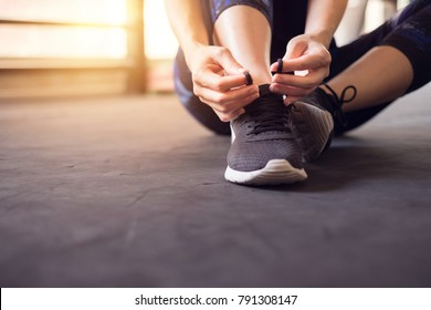Woman tying running shoes on black floor background in gym. copy space.