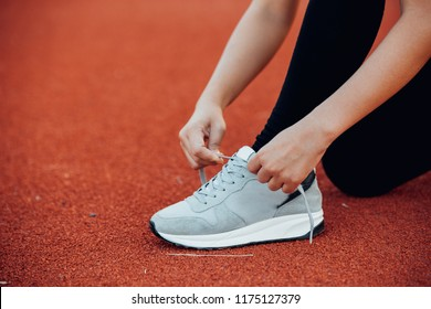 Woman tying shoe laces. Female sport fitness runner getting ready for jogging
