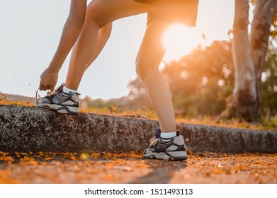 Woman tying shoe laces prepare to run.Female jogger getting ready for jogging outdoors on way. Jogging outdoors on forest.