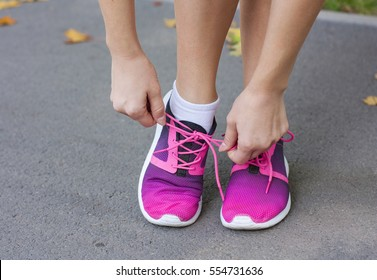 Woman tying shoelace on running shoes before practice.Fitness woman in training shoes jogging outdoors in park. Bright  running  shoes