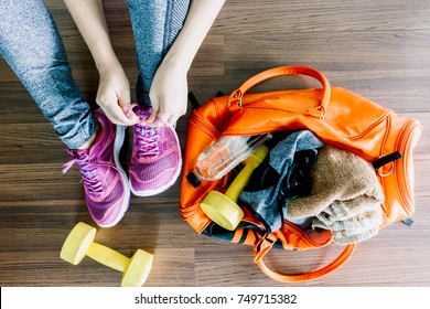 Woman tying shoelaces with bag and fitness equipment
