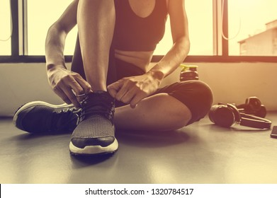 woman tying shoelaces at gym.