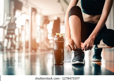 woman tying shoelaces at gym.young female at gym taking a break from workout.