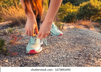 Woman tying shoelaces on sneakers. The concept of sports lifestyle and training. Copy space