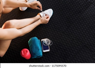 woman tying shoelaces of white trainers siting on a mat surrounded by mobile phone, earphones, towel and a shaker in the gym. top view