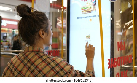 Woman types on fastfood restaurant interactive order board