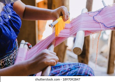 Woman in typical Guatemalan dress weaving with colored threads in the weaver - indigenous artisan woman from Guatemala making local weaving in a rural area
