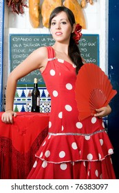 woman in typical spanish restaurant with flamenco dresses