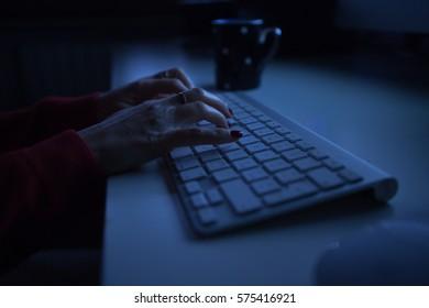 woman typing computer night light