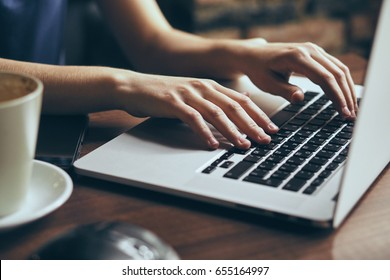 Woman is typing on a laptop