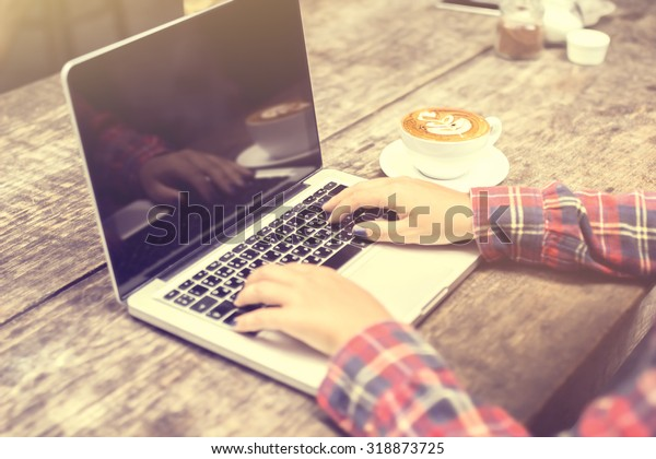 woman typing on a laptop with a cup of coffee at sunrise