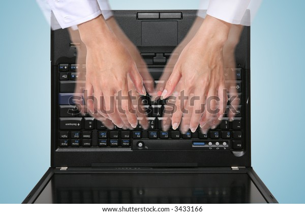 A woman typing on the laptop at a high rate of speed