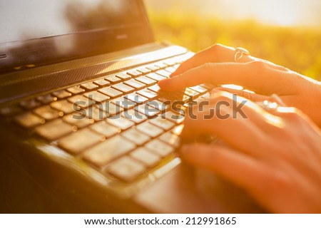 Woman typing on a laptop keyboard in a warm sunny day outdoors. Sunset. Copy Space