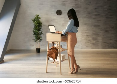 Woman typing on laptop at stand-up workplace