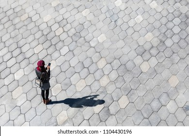 Woman typing on the phone, shadow and empty space. Minimal image, top view of a girl with a smartphone, and her shadow on the pavement. Technology concept, blank space to add text.
