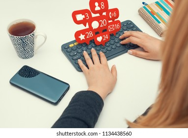 woman typing on wireless keyboard and notification icons of social network flying over keyboard