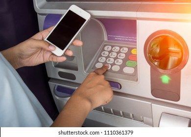 woman typing security PIN code you see on your phone the ATM to withdraw money