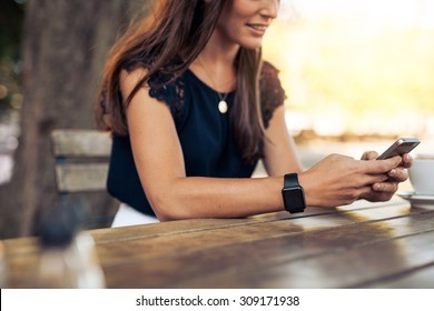 Woman typing text message on smart phone in a cafe. Cropped image of young woman sitting at a table with a coffee using mobile phone.