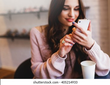 Woman typing write  message on smart phone in a  modern cafe. Cropped image of young  pretty girl sitting at a table with  coffee or cappuccino  using mobile phone.
