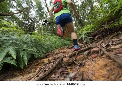 Woman ultra marathon runner running on tropical forest trail