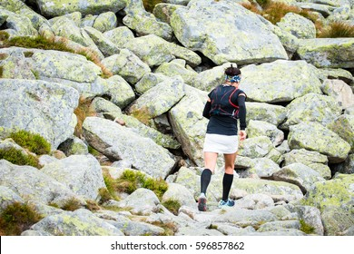 woman ultra trail runner training running in high mountains on track with stones