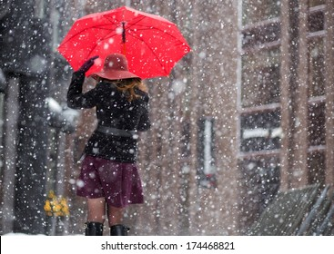 Woman with umbrella from behind walk on street