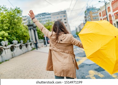 Woman with umbrella catching taxi. Hello taxi. Hailing a Taxi. Young girl with umbrella trying to stop a cab. Woman calling a taxi on a rainy day.
