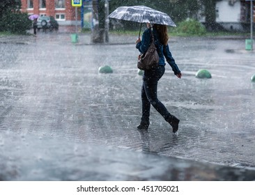 Woman with umbrella going on street during heavy rain .