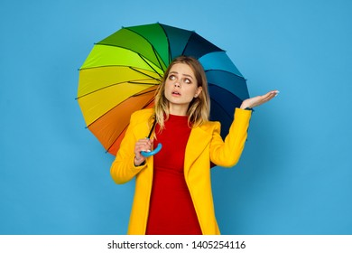 woman with an umbrella holds a place on her arm free on a blue background