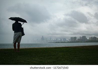 Woman with Umbrella Looking at Downtown Chicago during Rainstorm