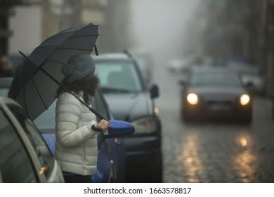A woman with an umbrella on a foggy city street.