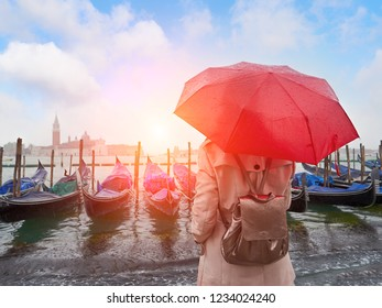 Woman with umbrella standing back and looking on gondolas. San Giorgio Maggiore church background. Venice. Italy