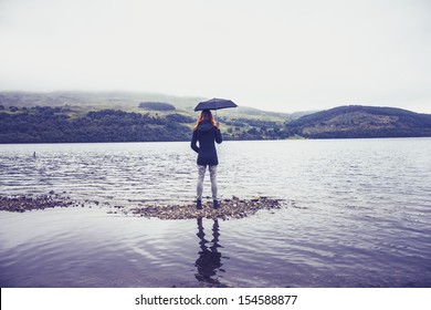 Woman with umbrella standing in lake