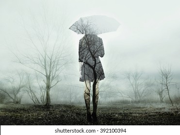 Woman with umbrella standing on the field with trees. The image with the effect of double exposure