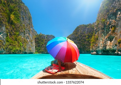 woman with an umbrella from the sun travels in the summer holidays on a boat among the islands of Phi Phi in Thailand.