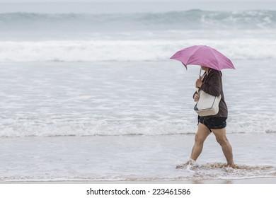 Woman with umbrella walking along the seashore