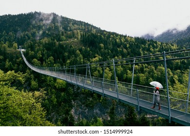 A woman with umbrella walking on beautiful landscape at suspension Bridge highline179 near Burgenwelt Ehrenberg at Reutte between 2 hills. Concept of challange, risk, brave, overcome fear.