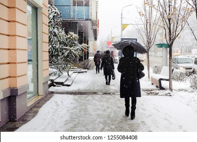 A woman with an umbrella is walking on a snow-covered sidewalk during a snowstorm, snowfall, sleet.