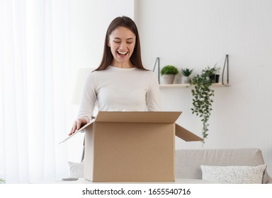 Woman unboxing cardboard box with protective foam pads inside after buying ordering online via internet a present
