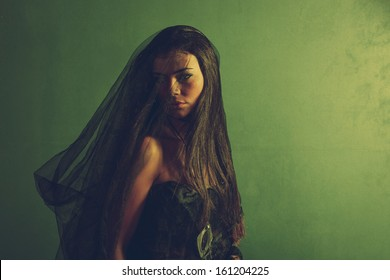woman under black veil in front green wall
